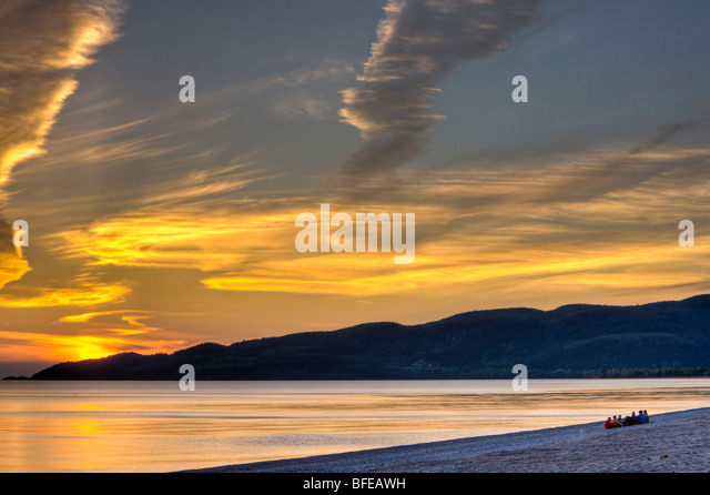 Group of people sitting on the beach in Agawa Bay at sunset, Lake Superior, Lake Superior Provincial Park, Ontario, - Stock Image