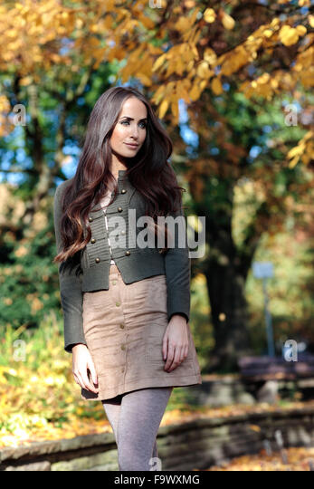Portrait of young woman with long brown hair in autumn - Stock Image
