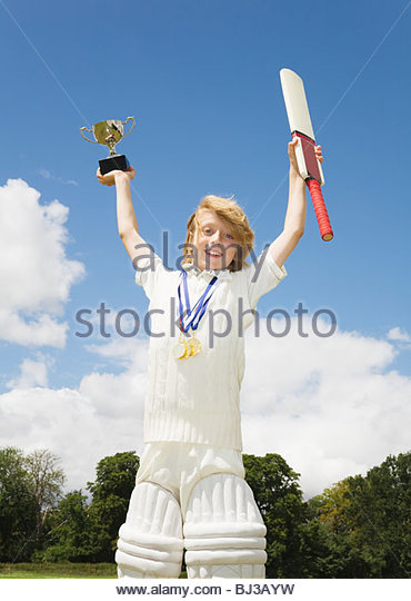 Boy with Cricket Bat, medals and Trophy - Stock Image