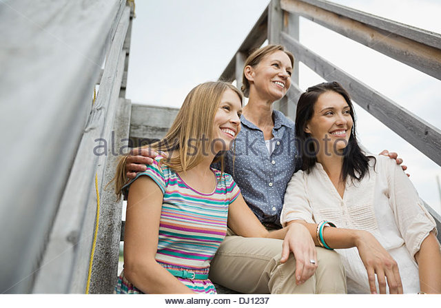 Low angle view of female family members sitting on steps - Stock Image