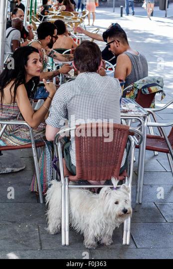 Spain Europe Spanish Madrid Centro Lavapias Calle Argumosa restaurant alfresco customers dog pet under table chair - Stock Image