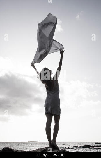 Woman standing on rock near ocean, holding fabric in the wind. - Stock Image