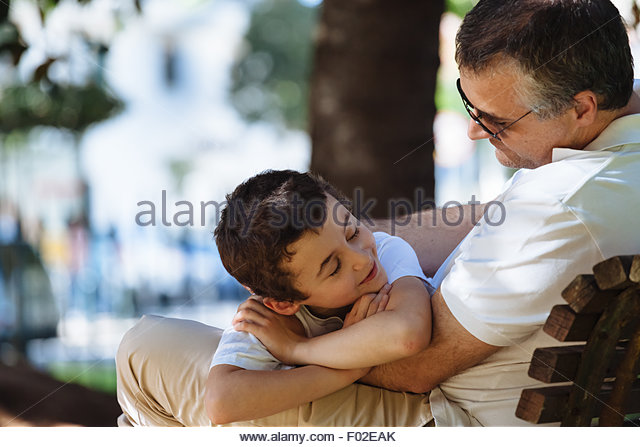 Father and son sitting on a park bench - Stock Image