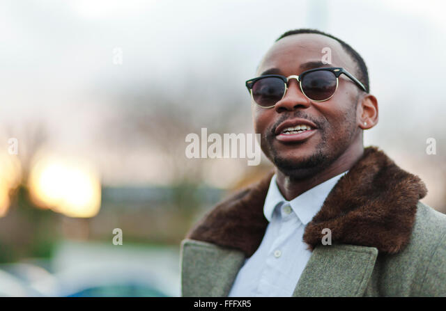 Black man looks away at sunset. - Stock Image