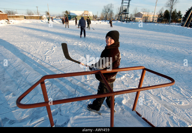 A young boy plays in goals during a game of ice hockey in rural Sakhalin Island Russia 2005 - Stock Image