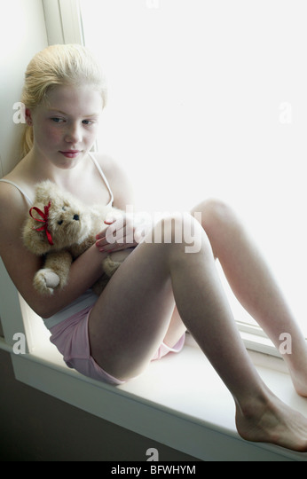 young girl sitting near window with stuffed animal - Stock Image
