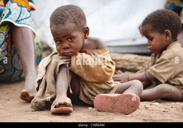 A child sits on the ground at the Miketo IDP settlement, Katanga province, Democratic Republic of Congo - Stock-Bilder