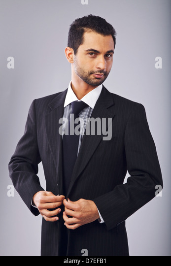 Young manager looking at you while buttoning his suit - Stock Image