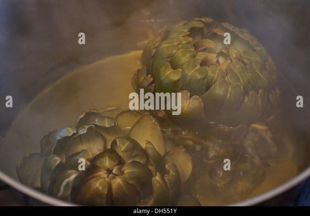 Boil  artichoke in water - Stock Image