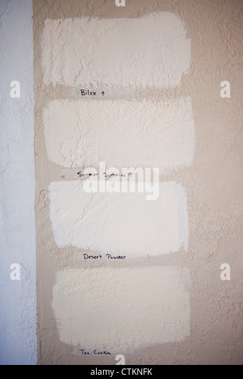Trying out a variety of paint colors on a wall and labeling with masking tape. - Stock Image