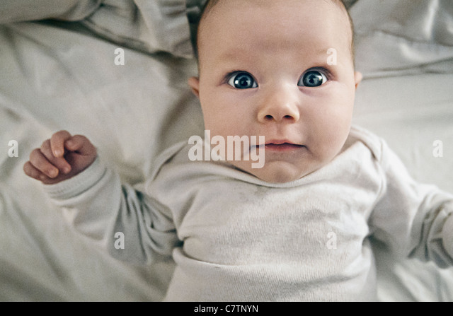3 Month old Baby Girl on Bed - Stock Image
