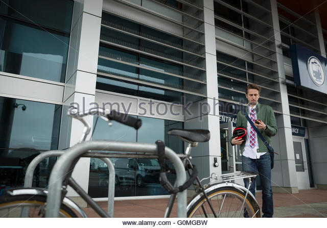 Businessman approaching bicycle secured to post - Stock Image