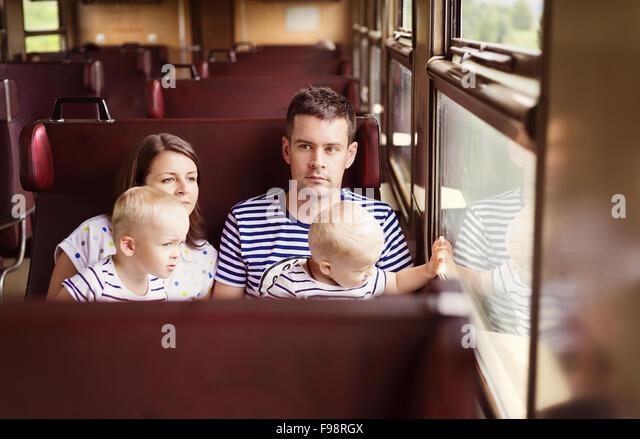 Family with two children travel in retro train. - Stock-Bilder
