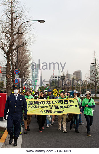 Greenpeace activists march with 10,000's of protesters on the Japanese parliament to call for an end to nuclear - Stock Image