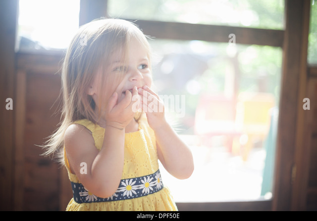 Close up of female toddler with hands over mouth - Stock Image