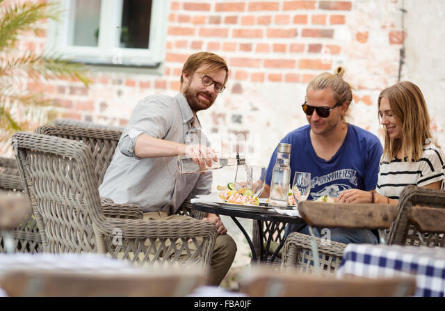 Sweden, Skane, Three people at cafe eating lunch - Stock Image