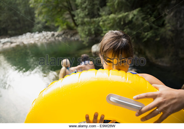 Portrait of woman hiding behind inflatable ring - Stock Image