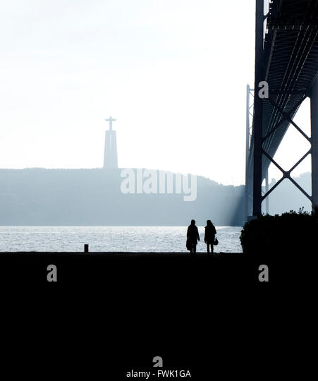 Friends Walking At Riverbank By April 25Th Bridge Against Christ The King Statue - Stock-Bilder