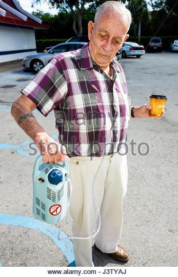 Florida Boynton Beach portable oxygen unit machine man senior breathing health lungs pulmonary disease illness breathing - Stock Image
