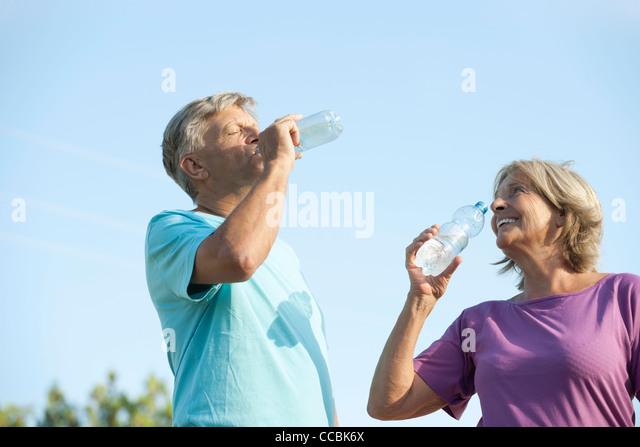 Senior couple drinking bottled water outdoors - Stock Image