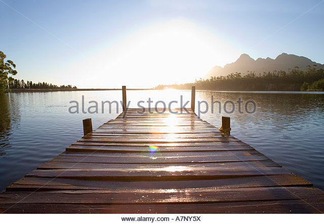 South Africa wooden jetty on tranquil lake at sunset lens flare - Stock Image