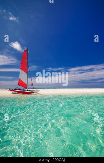 Sailing boat with red sail on beach of deserted tropical island - Stock Image