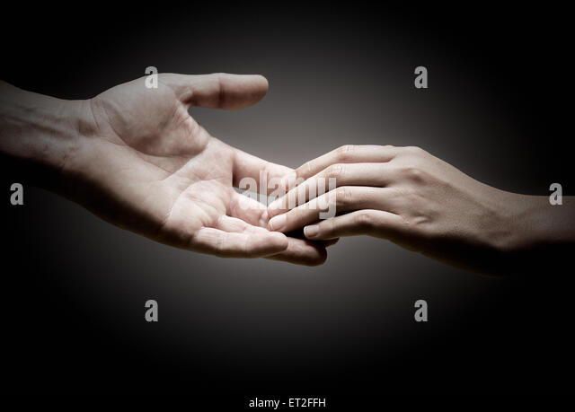 two hands are touching each other over black background, concept of solidarity or empathy. - Stock Image