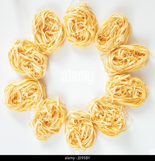 Italian Fettuccine nest pasta on light grey background - Stock Image