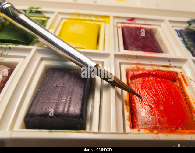 Closeup of brush poised above tablet of red water colour in a paint box. - Stock-Bilder