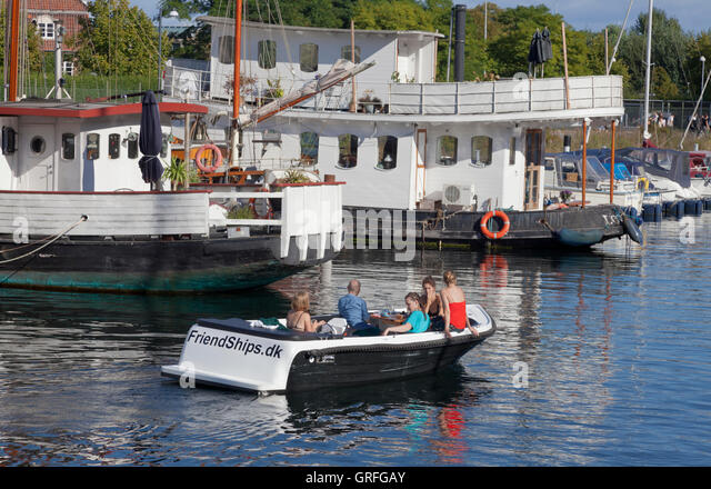 Young people on a picnic sailing trip in Christianshavn Canal in Copenhagen in rented boat returning to Friendships.dk - Stock Image