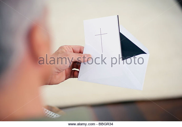 Close-up senior man holding card with cross - Stock Image