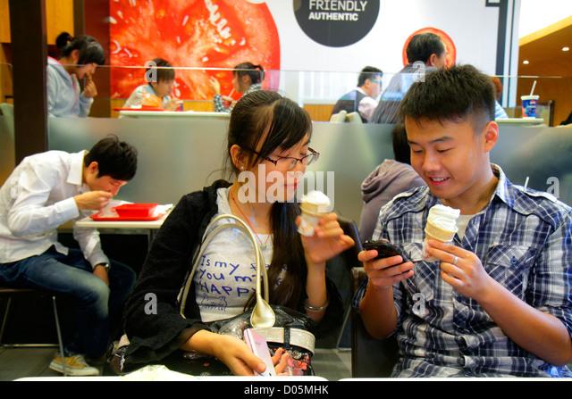Shanghai China Huangpu District Xizang Road People's Square Raffles City shopping Asian teen boy girl ice cream - Stock Image