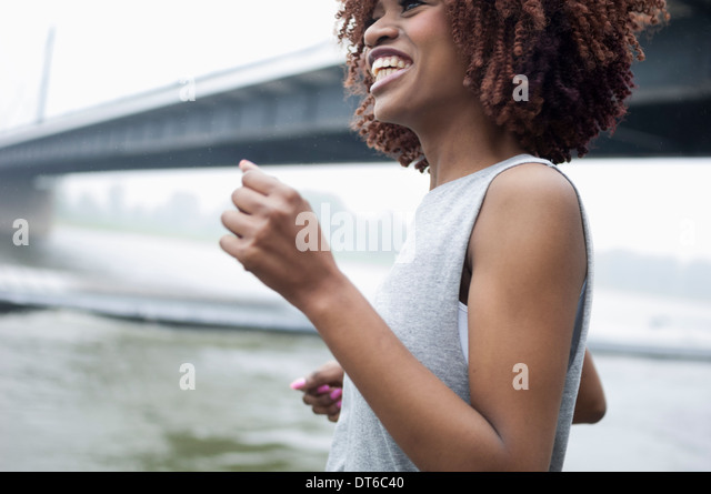 Young woman jogging by bridge, Dusseldorf, Germany - Stock-Bilder