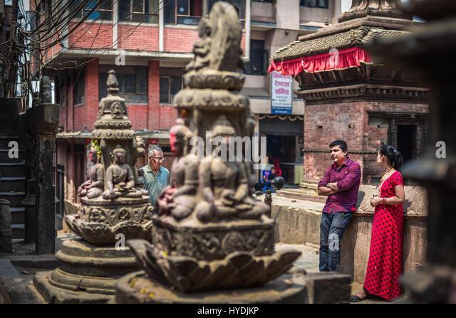 Local people having leisure time near Hindu sculptures at the residential neighborhood of Kathmandu, Nepal. © - Stock Image