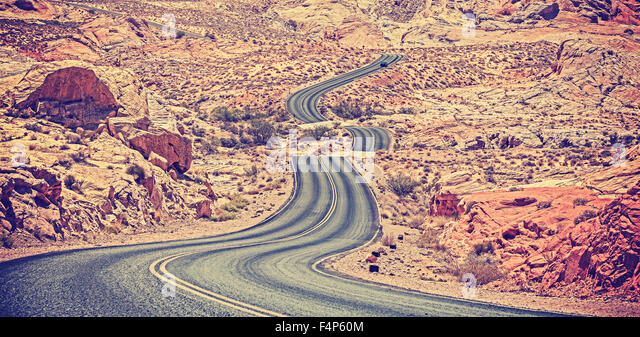 Vintage toned curved desert highway, travel adventure concept, USA. - Stock Image