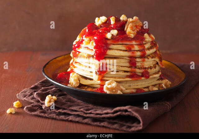 stack of pancakes with strawberry jam and walnuts. tasty dessert - Stock Image