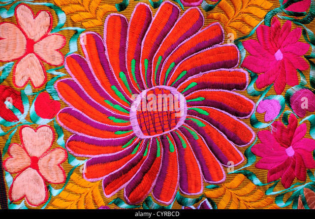 Mexico, Bajio, San Miguel de Allende, Brightly coloured embroidered textile hanging outside arts shop with flower - Stock-Bilder