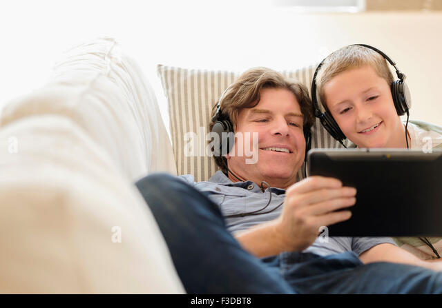 Man using tablet pc with his son (8-9) on sofa - Stock Image