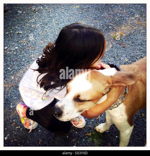 Little girl hugging her dog - Stock Image