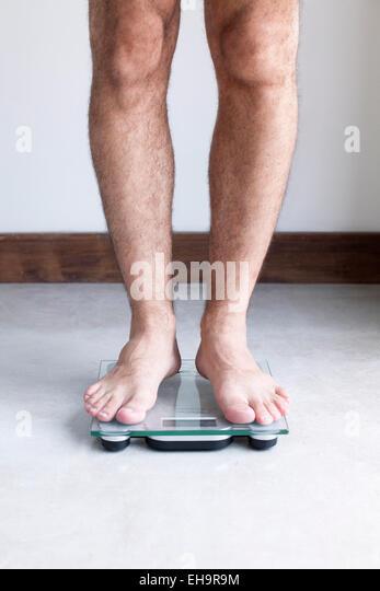 Man weighing self on bathroom scale - Stock-Bilder