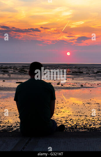 Southport, Merseyside, UK. 06-Jun-16.  UK Weather. A man watches the warm setting sun over the horizon after one - Stock Image
