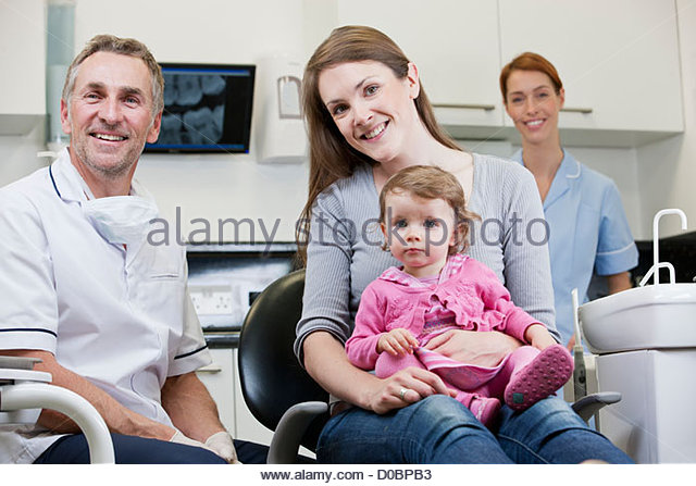 A male dentist with a little girl patient and her mother - Stock Image