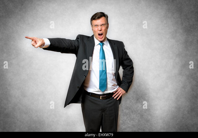 image of angry business man in suit who is screaming and pointing with finger - Stock Image
