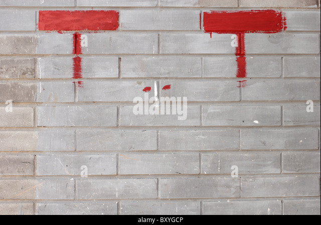 detail of a bricks wall with eye shaped painting - Stock Image