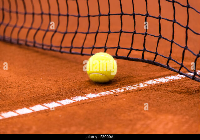 yellow tennis ball on a red clay court - Stock-Bilder