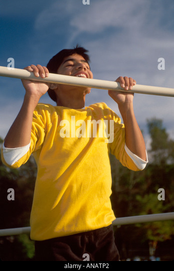 New Jersey Teaneck Asian boy teen pull up chin bar strength muscle effort - Stock Image