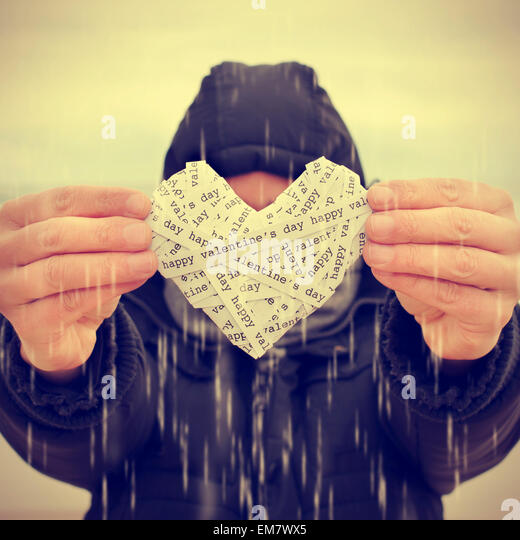 a young man under the rain showing a heart made-up with paper strips with the text happy valentines day, with a - Stock Image