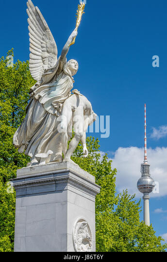 A warrior sculpture at the Schlossbrücke Unter den Linden with the 'Alex' in the background - Stock Image