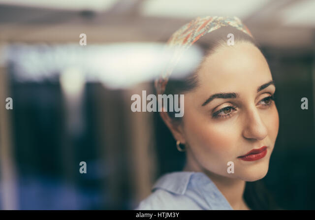 Horizontal indoors portrait of beautiful lady with face expressing exhaustion looking away. - Stock Image