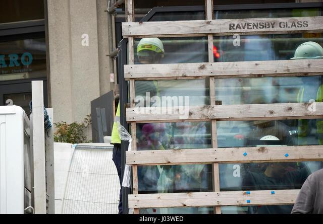 workmen delivering glass panels to commercial development city centre Liverpool UK - Stock Image
